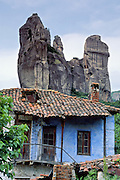 "Fantastic rock spires of Meteora rise above a blue house with red tile roof in Kastraki, near Kalambaka, in central Greece, Europe. Meteora (which means ""suspended in the air"") is a complex of six Eastern Orthodox Christian monasteries built by medieval monks on natural rock pillars near Kalambaka, in central Greece, Europe. The sandstone and conglomerate of Meteora were formed in the cone of a river delta estuary emerging into a sea about 60 million years ago, then later uplifted and eroded into pinnacles. The isolated monasteries of Meteora helped keep alive Greek Orthodox religious traditions and Hellenic culture during the turbulent Middle Ages and Ottoman Turk occupation of Greece (1453-1829). UNESCO honored Meteora as a World Heritage Site in 1988. Visit early in the morning and in the off season to avoid crowds. Published in ""Light Travel: Photography on the Go"" book by Tom Dempsey 2009, 2010."
