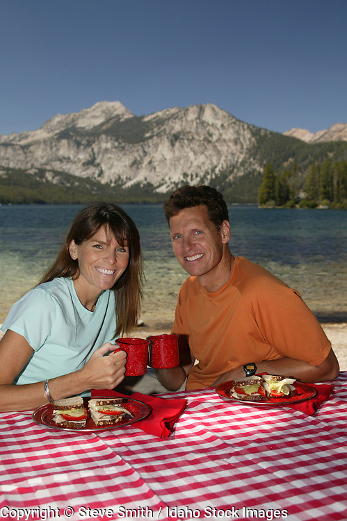 Idaho, Pettit Lake.  Couple enjoying a lakeside picnic north of Sun Valley in the Sawtooth Mountains.