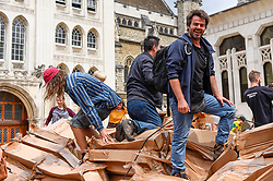 © Licensed to London News Pictures. 21/07/2019. LONDON, UK.  Members of the public tear apart The People's Tower, a monumental cardboard structure, built by artist Olivier Grossetête (pictured) aided by a local volunteers, which stood in Guildhall Yard.  Over 1,000 boxes were used to build the 20m high artwork, inspired by the Guildhall building.  The four day construction process culminates in the structure being ceremonially torn down.  Photo credit: Stephen Chung/LNP
