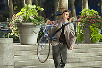 Man carrying bicycle down steps in park