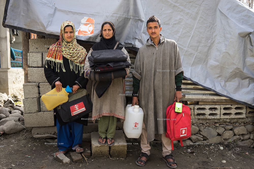 Shamima (centre), 35, stands with her son Sajad, 19, and daughter Shokeena, 17,  in front of their temporary shelter built using the Shelter kit given to them by Save the Children, in Purnishadashah village, Jammu and Kashmir, India, on 24th March 2015. Shamina is a widow who's house fell down during the floods. Save the Children supported the family with emergency shelter items like tarpaulin and other emergency relief kits for household, education, non-food items, and food baskets. Photo by Suzanne Lee for Save the Children