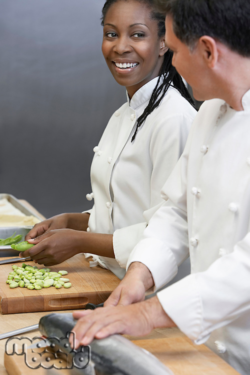Two chefs preparing salmon and vegetables in kitchen