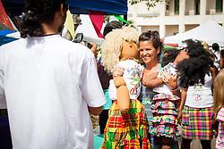 "Sondra Sechrist stops to take a picture with Karibbean Kids dolls.  ""Alvin's Cultural Workshop"" Cultural Fair honoring Mr. Alvin Turnbull.  Emancipation Garden.  St. Thomas, VI.  29 April 2015.  © Aisha-Zakiya Boyd"