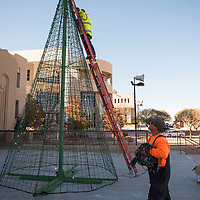 City of Gallup Parks and Recreation workers Matthew Retan (right), and Odie Garcia (on ladder) putting  Christmas decorations up in the McKinley County Courthouse Square, Monday Nov. 19 in Gallup.
