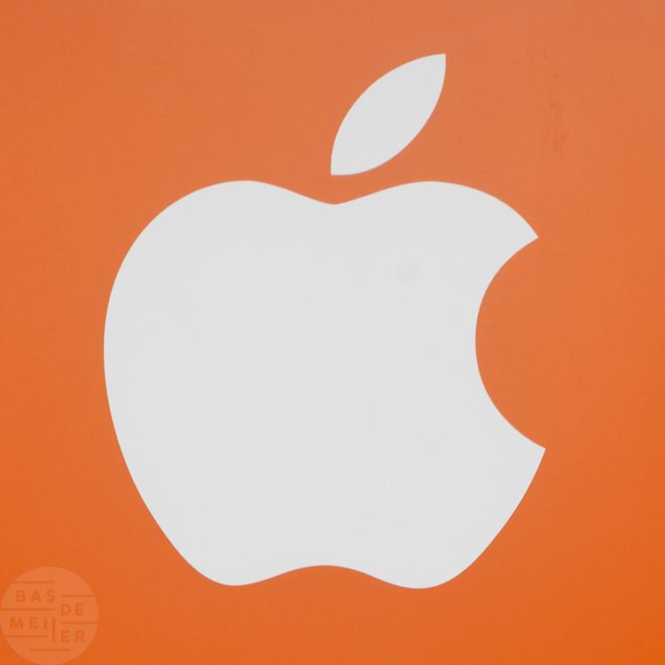 Het logo van Apple met een oranje achtergrond. Op het Leidseplein in Amsterdam wordt de laatste werkzaamheden verricht voor de eerste Apple Store in Nederland die op 3 maart 2012 wordt geopend.<br /> <br /> The last preparations for the Apple Store in Amsterdam, which will open March 3rd, 2012.