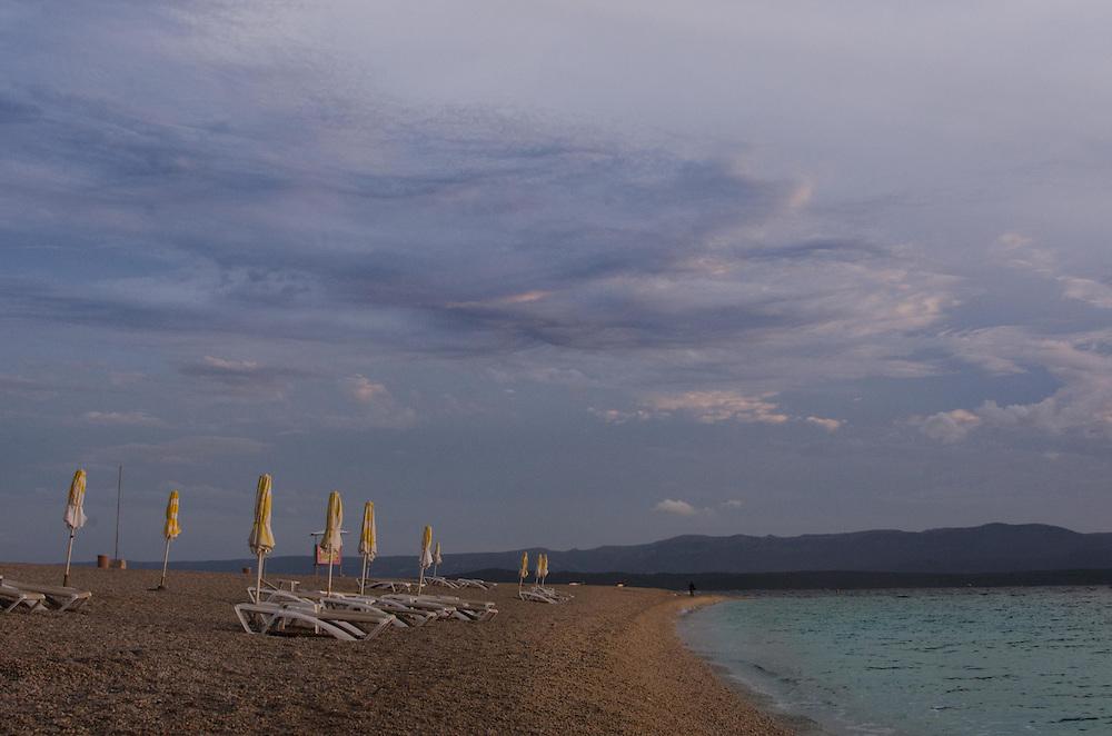 Rolled up umbrellas on Zlatni Rat Beach, Bracč Croatia