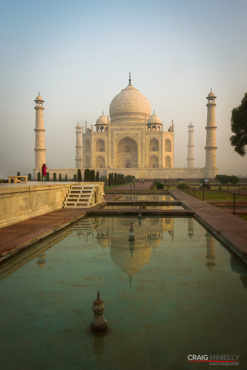 Sunrise at the Taj Mahal, reflected in pool, with tourist woman in red dress<br /> <br /> Nikon D750 32mm  ISO 1000  f14  1/250s