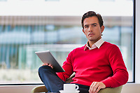 Portrait of attractive businessman using digital tablet while sitting and drinking coffee in lobby
