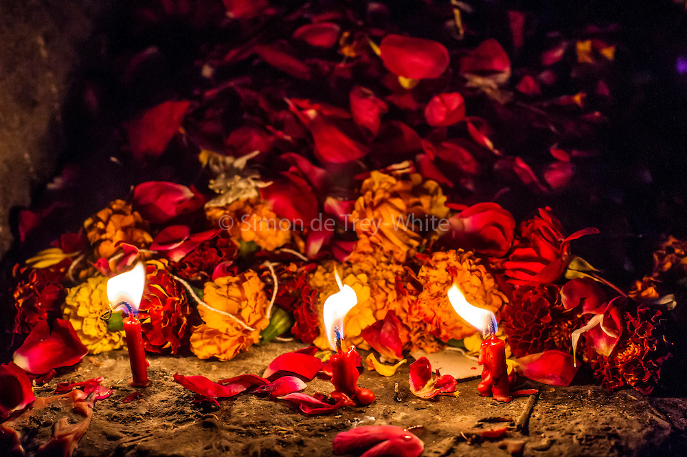 8th January 2015, New Delhi, India.Three red candles burn in front to of a mound of flower petals left by believers hoping to get wishes granted by Djinns in the ruins of Feroz Shah Kotla in New Delhi, India on the 8th January 2015<br /> <br /> PHOTOGRAPH BY AND COPYRIGHT OF SIMON DE TREY-WHITE a photographer in delhi<br /> + 91 98103 99809. Email: simon@simondetreywhite.com<br /> <br /> People have been coming to Firoz Shah Kotla to leave written notes and offerings for Djinns in the hopes of getting wishes granted since the late 1970's. Jinn, jann or djinn are supernatural creatures in Islamic mythology as well as pre-Islamic Arabian mythology. They are mentioned frequently in the Quran  and other Islamic texts and inhabit an unseen world called Djinnestan. In Islamic theology jinn are said to be creatures with free will, made from smokeless fire by Allah as humans were made of clay, among other things. According to the Quran, jinn have free will, and Iblīs abused this freedom in front of Allah by refusing to bow to Adam when Allah ordered angels and jinn to do so. For disobeying Allah, Iblīs was expelled from Paradise and called &quot;Shayṭān&quot; (Satan).They are usually invisible to humans, but humans do appear clearly to jinn, as they can possess them. Like humans, jinn will also be judged on the Day of Judgment and will be sent to Paradise or Hell according to their deeds. Feroz Shah Tughlaq (r. 1351&ndash;88), the Sultan of Delhi, established the fortified city of Ferozabad in 1354, as the new capital of the Delhi Sultanate, and included in it the site of the present Feroz Shah Kotla. Kotla literally means fortress or citadel.