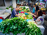24 AUGUST 2018 - GEORGE TOWN, PENANG, MALAYSIA: Customers at a produce stand in Chowrasta Market in central George Town. Chowrasta Market was originally built in 1890 and is the older of two traditional markets in George Town. The original building was torn down and replaced with a modern building in 1961 and has been renovated several times since.     PHOTO BY JACK KURTZ