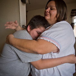 Lane Miller, 12 hugs his mother Kami inside their home on the Moapa reservation in Nevada. Lane has trouble breathing and uses an inhaler and nebulizer for his lungs. Sierra Club is working with the Moapa Band of Paiutes to transition NV Energy away from the Reid Gardner coal-fired power plant -- which sits only 45 miles from Las Vegas and a short walk from community housing at the Moapa River Indian Reservation. The Reid Gardner coal plant is literally spewing out tons of airborne pollutants such as mercury, nitrous oxide, sulfur dioxide, and greenhouse gases. This has resulted in substantial health impacts on the Moapa community, with a majority of tribal members reporting a sinus or respiratory ailment.