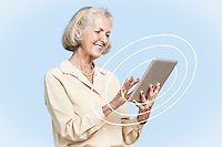 Happy senior woman using tablet PC against blue background