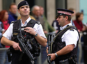 Armed policemen with bullet-proof vests (flak jackets) and machine guns are on guard in London