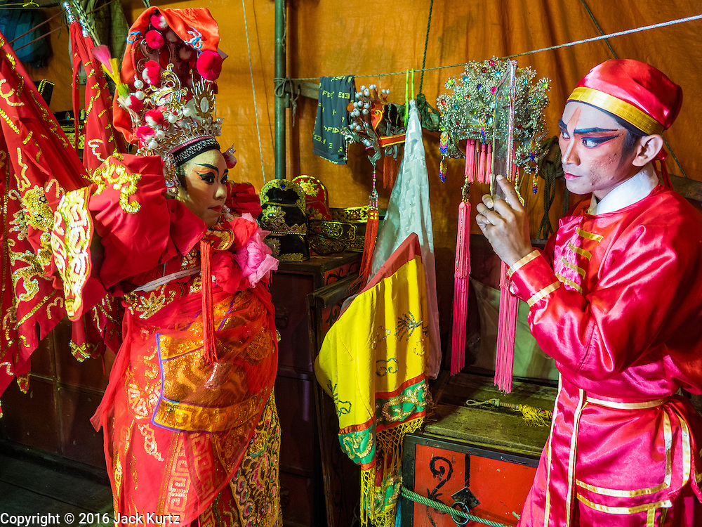 17 FEBRUARY 2016 - BANGKOK, THAILAND: A Chinese opera performer checks her makeup and costume in a mirror held up by another member of the troupe. The small troupe travels from Chinese shrine to Chinese shrine performing for a few nights before going to another shrine. They spend about half the year touring in Thailand and the other half of the year touring in Malaysia. Members of the troupe are paid about 5,000 Thai Baht per month (about $140 US). Chinese opera was once very popular in Thailand, where it is called Ngiew. It is usually performed in the Teochew language. Millions of Chinese emigrated to Thailand (then Siam) in the 18th and 19th centuries and brought their culture with them. Recently the popularity of ngiew has faded as people turn to performances of opera on DVD or movies. There are still as many 30 Chinese opera troupes left in Bangkok and its environs. They are especially busy during Chinese New Year and Chinese holiday when they travel from Chinese temple to Chinese temple performing on stages they put up in streets near the temple, sometimes sleeping on hammocks they sling under their stage. Most of the Chinese operas from Bangkok travel to Malaysia for Ghost Month, leaving just a few to perform in Bangkok.     PHOTO BY JACK KURTZ
