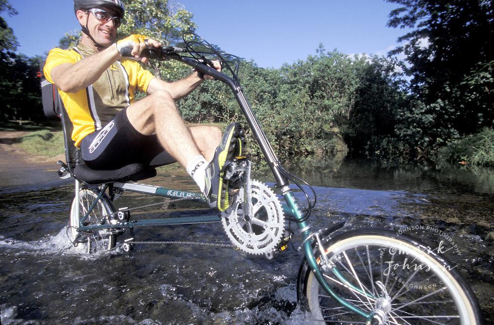 Man on recumbent bike crossing stream, Kauai, Hawaii