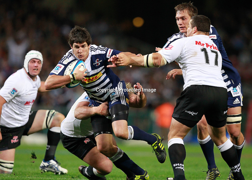 Sharks prop Jannie du Plessis (C-L) tackles Stormers centre Jaque Fourie (C) during their Super Rugby match in Cape Town, South Africa 30 April 2011