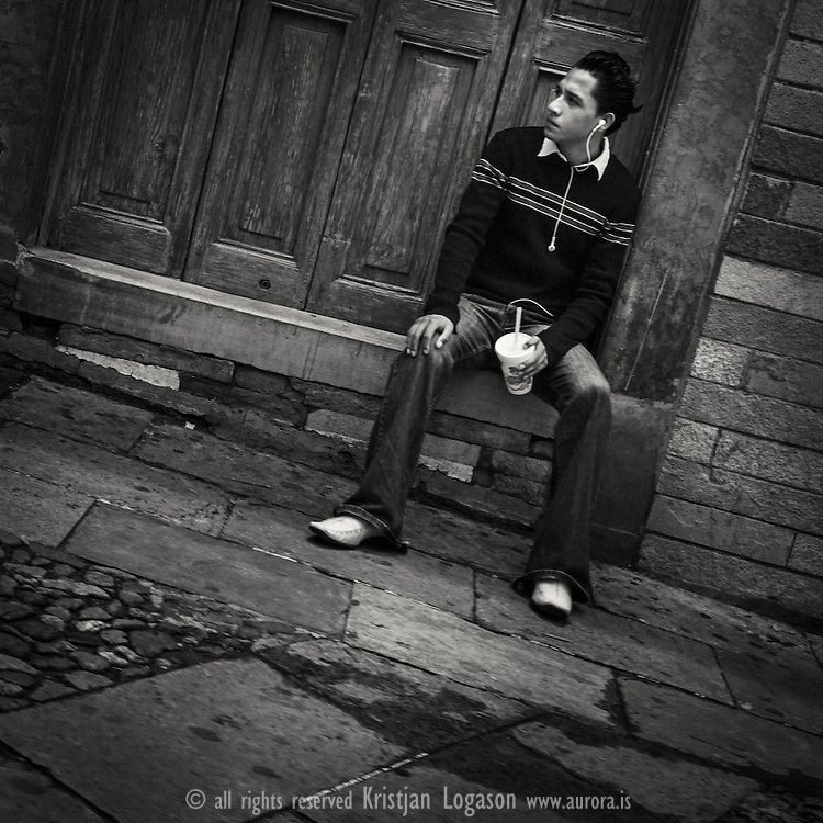 Man with headphones in his ear and a drink in hand sits in a doorway observing the street life around him in Guanajuato