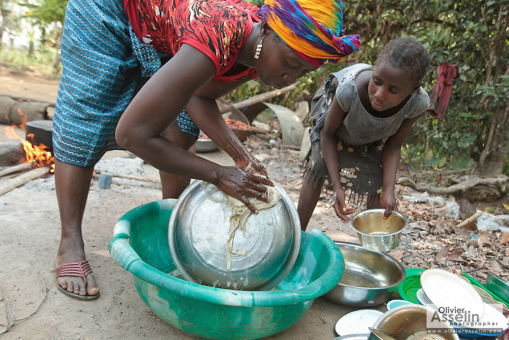 Tarah, 7, helps her mother Edith Saysay, 35, clean dishes  outside their home in the village of Jenneh, Bomi county, Liberia on Tuesday April 3, 2012. As part of a UNICEF sponsored social cash transfer programme, Edith and her family receive 2650 Liberian dollars (approx. 36 USD) per month. The money has allowed her to buy cassava from which she makes fufu that she then sells for profit. She also uses some of the money to send all of her seven children to school. Before joining the programme, only 3  of her children attended school.