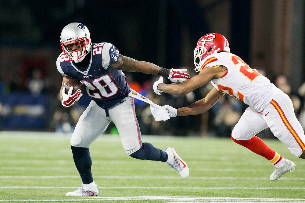New England Patriots running back James White (28) slips a tackle from Kansas City Chiefs cornerback Marcus Peters (22) in the third quarter of the AFC Divisional Playoff game at Gillette Stadium in Foxborough, Massachusetts on January 16, 2016. The Patriots defeated the Chiefs, 27-20.    Photo by Kelvin Ma/ UPI