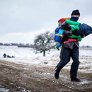 A refugee carries a child across the Macedonian-Serbian border. They are among nearly 70,000 refugees and migrants who arrived on the shores of Greece in January 2016, the majority of who traveled the route through Serbia on their way to Western Europe.<br /> Over the winter of 2016 Macedonia and Serbia limited entry to Afghan, Iraqi, and Syrian refugees. The Balkan borders have been closed to all refugees and migrants since March 2016. Produced for Mercy Corps.