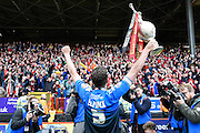 Tommy Elphick celebrates in front of Bournemouth fans after winning the Sky Bet Championship trophy after the Sky Bet Championship match between Charlton Athletic and Bournemouth at The Valley, London, England on 2 May 2015. Photo by David Charbit.