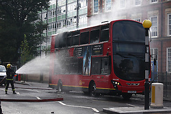© licensed to London News Pictures. London, UK. 08/08/11. Firemen hose down a bus set on fire on Peckham Road, Camberwell, London which was set alight during rioting today (08/08/2011). Photo credit should read Sam Bush/LNP