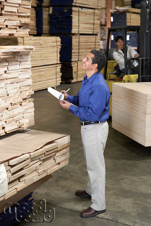 Man checking notes in warehouse full of wood