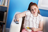 Overweight girl (13-15) Eating Junk Food holding remote control