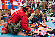 Ethnic Hmong hilltribe women are selling goods at a street market in Luang Prabang, Laos. Luang Prabang is a UNESCO World Heritage City.
