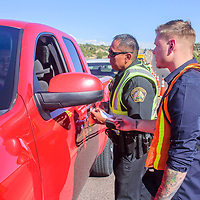 McKinley County Sheriff's Deputy Monty Yazzie and Domnick Riffle, with the McKinley County DWI Program, talk to a motorist and hand out promotional items during a DWI Joint Task Force Checkpoint Tuesday afternoon on New Mexico Highway 602 near Park Avenue in Gallup.