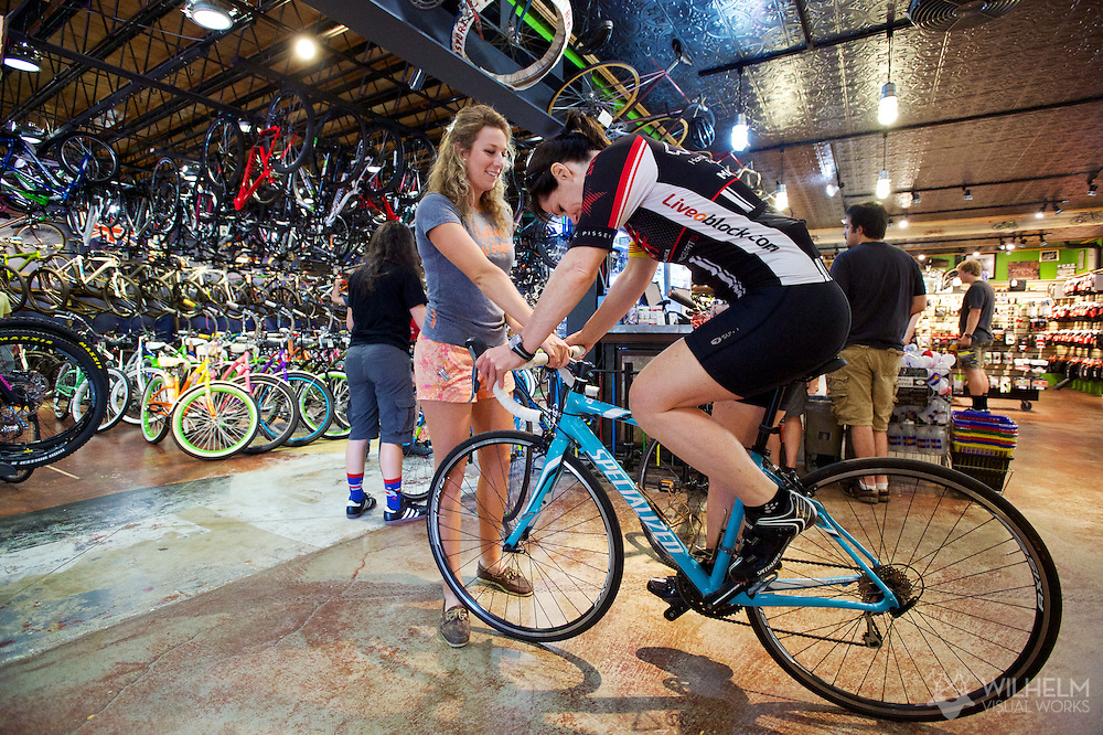 Shop employee Hillary Wight assists Lissie Stagg of Charlotte (formerly of Boulder, on a return visit) with a bike adjustment at University Bicycles in Boulder, CO. © Brett Wilhelm