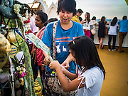 21 NOVEMBER 2015 - BANGKOK, THAILAND: A woman and her daughter donate 20Baht (about $0.60 US) at the Wat Saket temple fair. Wat Saket is on a man-made hill in the historic section of Bangkok. The temple has golden spire that is 260 feet high which was the highest point in Bangkok for more than 100 years. The temple construction began in the 1800s in the reign of King Rama III and was completed in the reign of King Rama IV. The annual temple fair is held on the 12th lunar month, for nine days around the November full moon. During the fair a red cloth (reminiscent of a monk's robe) is placed around the Golden Mount while the temple grounds hosts Thai traditional theatre, food stalls and traditional shows.     PHOTO BY JACK KURTZ