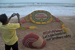 "August 6, 2017 - Puri, Orissa, India - A visitor taking pictures of a sand art, creating by sand artist Sudarshan Pattnaik on the eve of Indian Hindu festival ""Rakha Bandhan"" at the Bay of Bengal Sea's eastern coast beach at Puri, 65 km away from the eastern Indian state Odisha's capital city Bhubaneswar. ""Rakhya Bandhan"" is a festival in India every un married girls ties threads into their brother's hand for their safety in the society. (Credit Image: © Str/NurPhoto via ZUMA Press)"