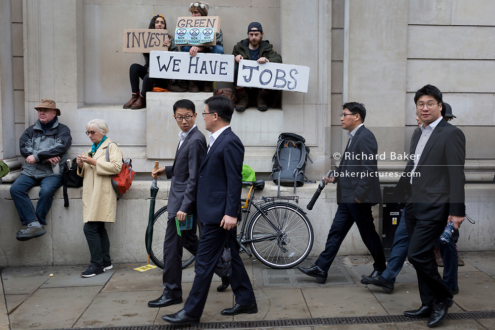 Asian businessmen look at environmental activists protesting about Climate Change during the blockade outside the Bank of England in the heart of the capital's financial district, the City of London aka the Square Mile, on the seventh day of a two-week prolonged worldwide protest by members of Extinction Rebellion, on 14th October 2019, in London, England.