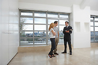 Real estate agent showing couple new apartment