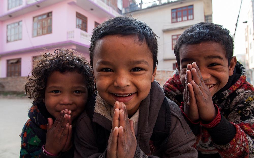 Three children make the traditional Nepali greeting.