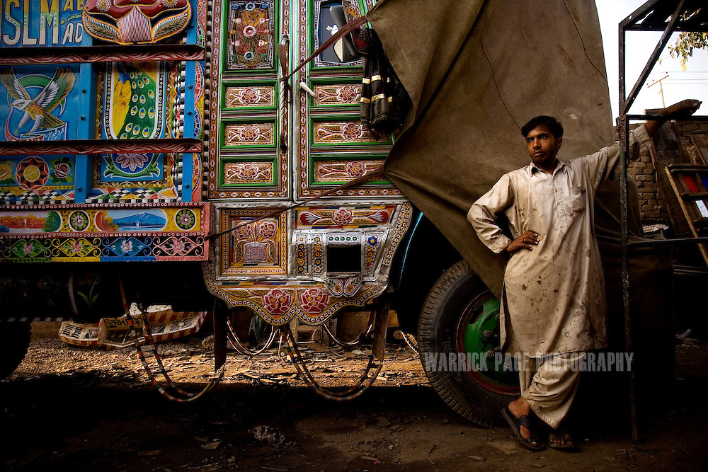 RAWALPINDI, PAKISTAN - OCTOBER 9: A mechanic takes rest at the end of the day at a painting and repair yard, October 9, 2008, in Rawalpindi, Pakistan. The heavily adorned Bedford trucks have become a national icon and cost upwards of one million rupees (USD$12,500) for a full makeover. Much of the artwork consists of a cultural mix of religious and secular, Pakistani film and music stars, cricket legends, romanticized military imagery of F-16 fighter jets and Ghauri missiles, the Prophet's winged horse, Buraq, and dreamlike scenes of wooded lakes and snow-capped mountains and exotic animals. (Photo by Warrick Page)