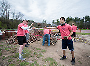 Volunteers pass bricks to one another while cleaning up the back yard of The Dairy Arts Barn during Athens Beautification Day on Sunday, April 22th 2018.