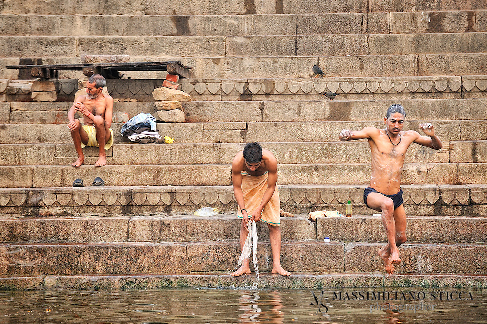 Pilgrims on the ghat of Varanasi praying before morning bath and washing clothes at River Ganges.
