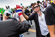 24 NOVEMBER 2013 - BANGKOK, THAILAND:  Thai anti-government protestors high five each other as they walk along Ratchdamnoen Ave in Bangkok. More than 400,000 people packed onto Ratchdamnoen Ave in Bangkok Sunday, continuing an anti-government protest that started weeks ago over a blanket amnesty bill passed by the Thai Parliament. The amnesty bill was defeated in the Thai Senate and the protest morphed into a general protest against the government. The protestors are allied with the Thai Democrat party, the opposition party in parliament. Tens of thousands of pro-government Red Shirts have come to Bangkok to defend the government and are rallying in a different part of the city. Police have warned of clashes between the two groups but as of Sunday evening no problems had been reported.     PHOTO BY JACK KURTZ