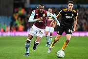 Aston Villa striker Jonathan Kodjia (26) sprints forward with the ball  under pressure from Wolverhampton Wanderers defender Max Kilman (49) during the EFL Cup match between Aston Villa and Wolverhampton Wanderers at Villa Park, Birmingham, England on 30 October 2019.
