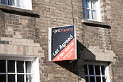 JSM Property Let Agreed estate agents sign on building, Woodbridge, Suffolk, England