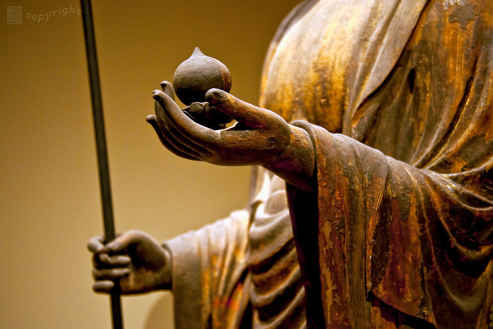 A detail of a Buddha statue holding a lotus.