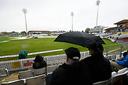 Umbrellas are up in the stands as a shower passes over during the delay in play during the Specsavers County Champ Div 1 match between Somerset County Cricket Club and Essex County Cricket Club at the Cooper Associates County Ground, Taunton, United Kingdom on 25 September 2019.