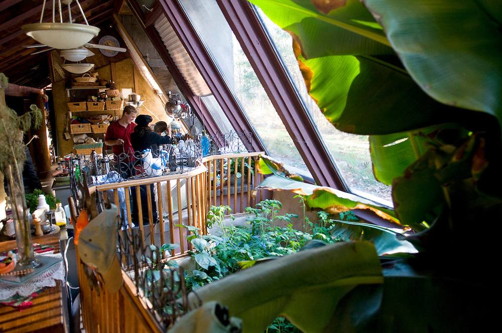 "Each end of the Earthship contains a ""wetlands"" or indoor garden area that is home to plants such as a banana and avocado tree, tomato plants, poinsettias, and other flowers."