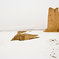 Man taking picture of the Kizilgaha Beacon Tower. Ku Che County, Xinjiang, China.