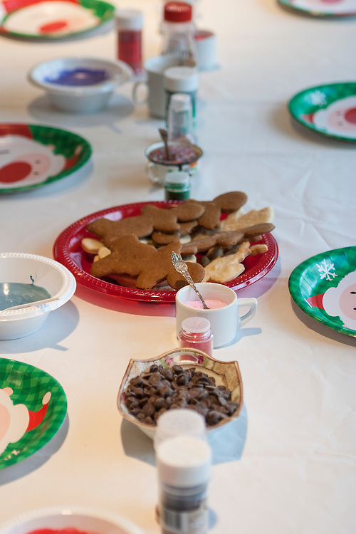 Table set with plates, icing, toppings and sugar cookies await children to begin holiday cookie decorating party