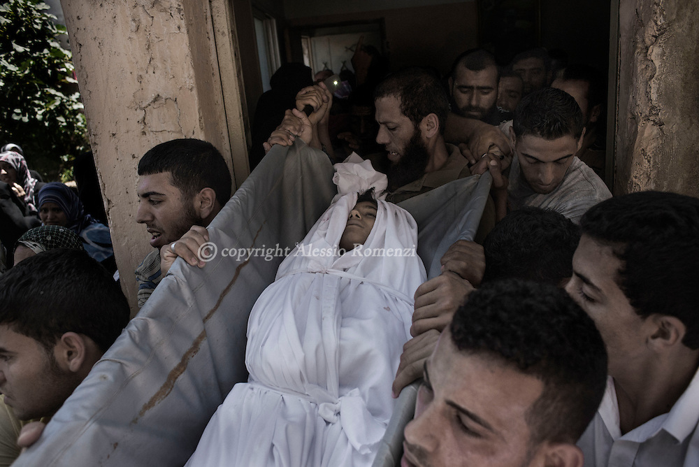 Gaza Strip, Beit Hanun: Relatives of Mohammed Masri (9 yo), killed along with his mother by Israeli airstrike on July 9, 2014, carried his body out of his house in Beit Hanun (north of Gaza Strip). ALESSIO ROMENZI