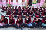 Pupils are having breakfast in the early hours of the morning inside the Jamoniya Tank Girls Hostel, near Sehore, Madhya Pradesh, India, where the Unicef India Sport For Development Project has started in 2012. Covering 313 state-run girls' hostels and 207 mixed hostels in Madhya Pradesh, the project ensures that children from Scheduled Tribes (ST) and others amongst the poorest people in India, can easily access education and be introduced to sports. Field workers from Unicef also oversee their nutrition and monitor the overall conditions of each pupil.