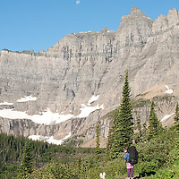 woman hiker in outdoor cloths, hiking iceberg lake trail, glacier national park, montana, crown of the continent, many glacier valley